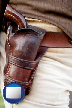 a gun in a Western-style, leather holster - with Wyoming icon